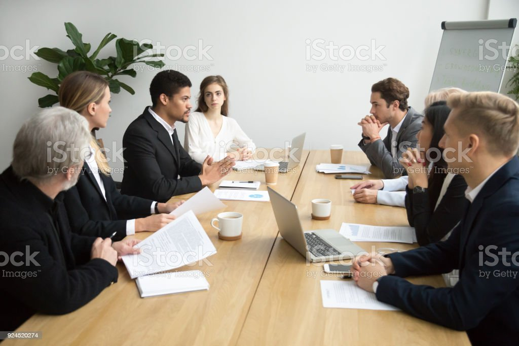 Focused black team leader talking to colleagues at meeting sitting at...