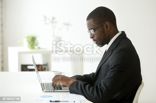 872006502 istock photo Focused black worker working at laptop at company workplace 974640748