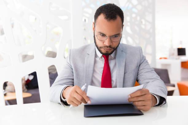集中したビジネスマンの読書契約 - パラリーガル ストックフォトと画像