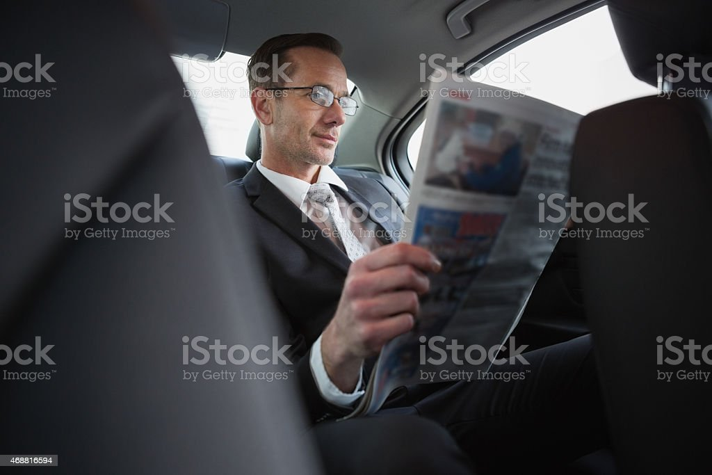 Focused businessman reading the newspaper stock photo