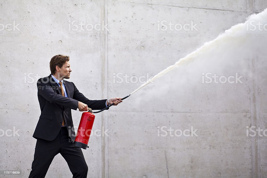 Focused businessman using a fire extinguisher stock photo