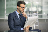 Focused businessman with glasses reading newspaper.