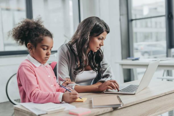 femme d'affaires ciblée travaillant sur ordinateur portable tout en fille dessin sur autocollant - femmes actives photos et images de collection