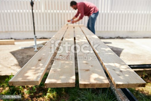 Skilled mid adult carpenter working on a new wooden fence, varnishing timber with protective paint