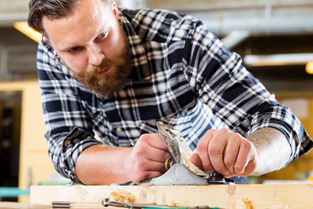 konzentriert schreiner arbeiten mit flugzeug auf holz plank in workshops - baroque tattoo stock-fotos und bilder
