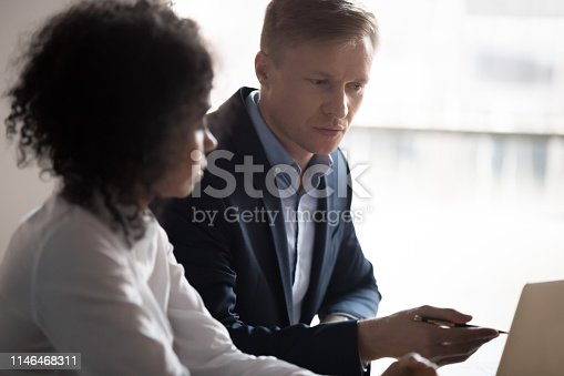 926404274 istock photo Focused caucasian mentor training african intern consulting client with laptop 1146468311