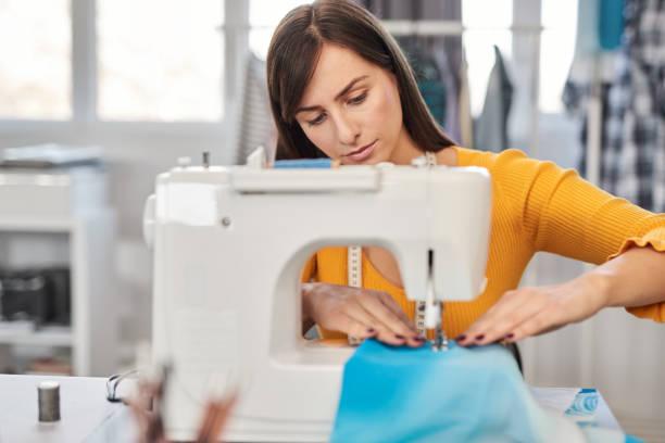Fokussiert charmante kaukasische Modedesignerin sitzt in ihrem Studio und nähet schöne Abendkleid. – Foto