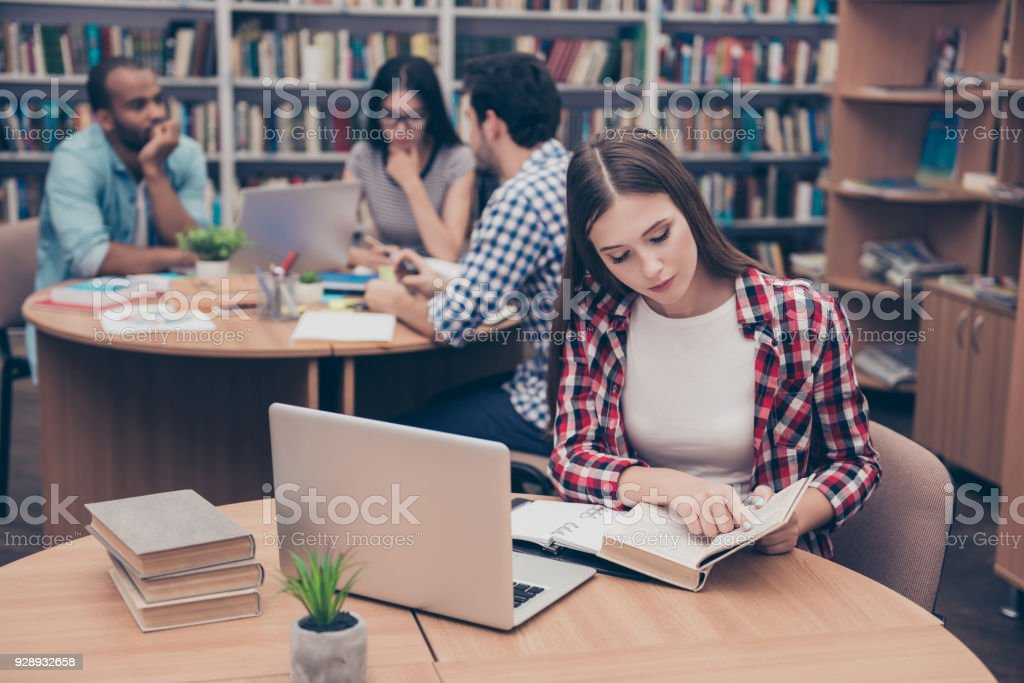 Focused concentrated attractive clever female student is learning with thesaurus in hard bookcase, wearing casual checkered shirt, behind her are classmates, book shelves of campus library stock photo
