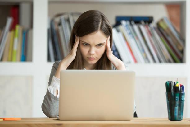enfocado el examen difícil con el ordenador portátil en línea de aprendizaje de los estudiantes interesados chica - concentración fotografías e imágenes de stock