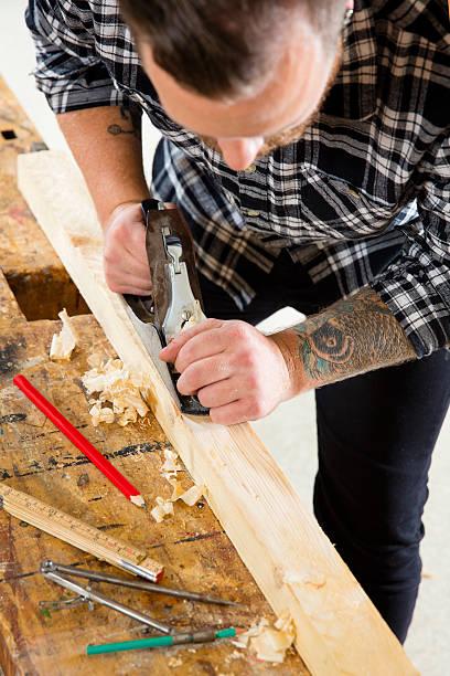 konzentriert handwerker arbeiten mit flugzeug auf holz plank in workshops - baroque tattoo stock-fotos und bilder