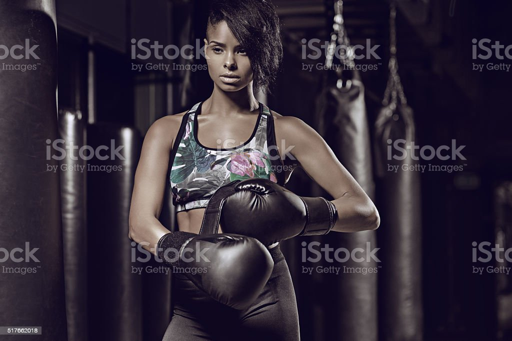 Focused dark haired female preparing at boxing gym stock photo
