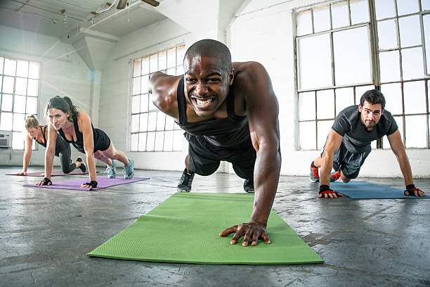 Focused determined powerful strong fitness workout push ups gritting teeth Focused determined powerful strong men fitness workout push ups gritting teeth Gritty gym group exercise fitness class man with passion is strong leader Fit man with big muscles exercising fitness with one armed push ups strong powerful intensity clenching teeth stock pictures, royalty-free photos & images