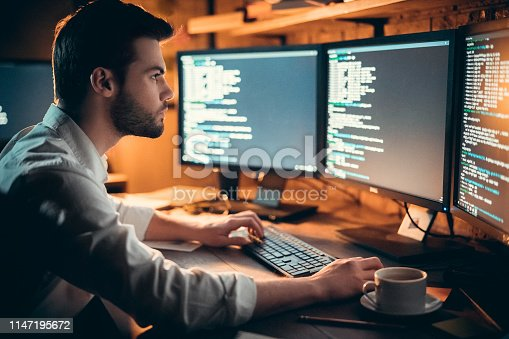 istock Focused developer coding on computer monitors working late in office 1147195672