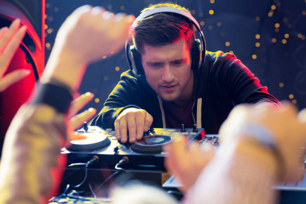 Focused DJ playing Young handsome focused DJ playing at the club electronic music stock pictures, royalty-free photos & images