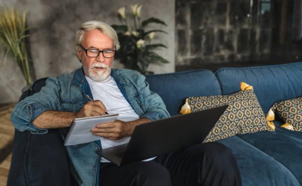 fokussierter älterer mann schreiben notizen in notebook beobachten webinar oder online-training mit laptop-computer moderne senior männlich mit grauen haaren und bart lernen online - einzelner senior stock-fotos und bilder