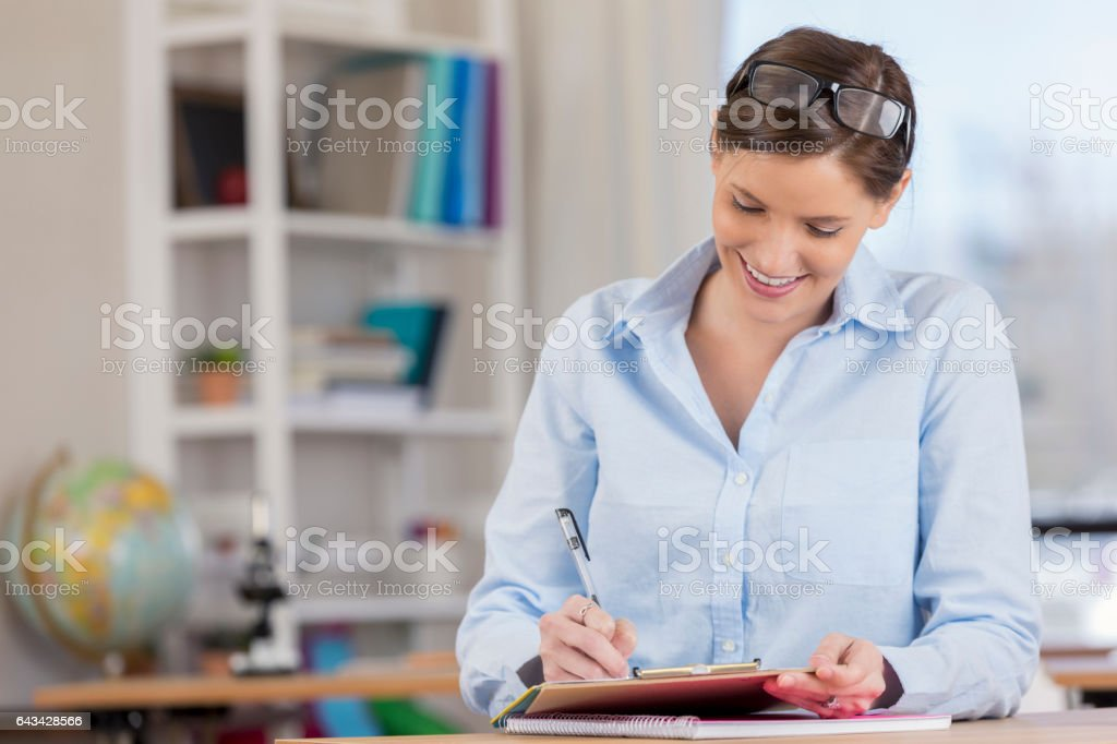 Focused elementary school teacher grades papers before class stock photo