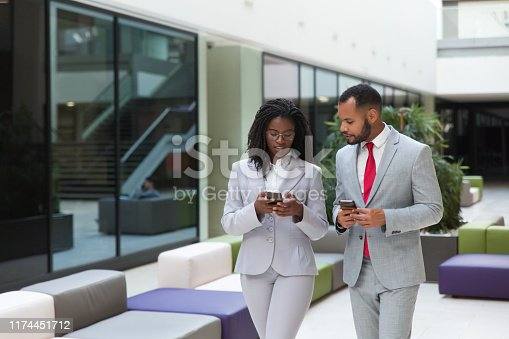Focused excited business colleagues using mobile phones while discussing work issues. Business man and woman walking through office hallway and holding smartphones. Wireless communication concept