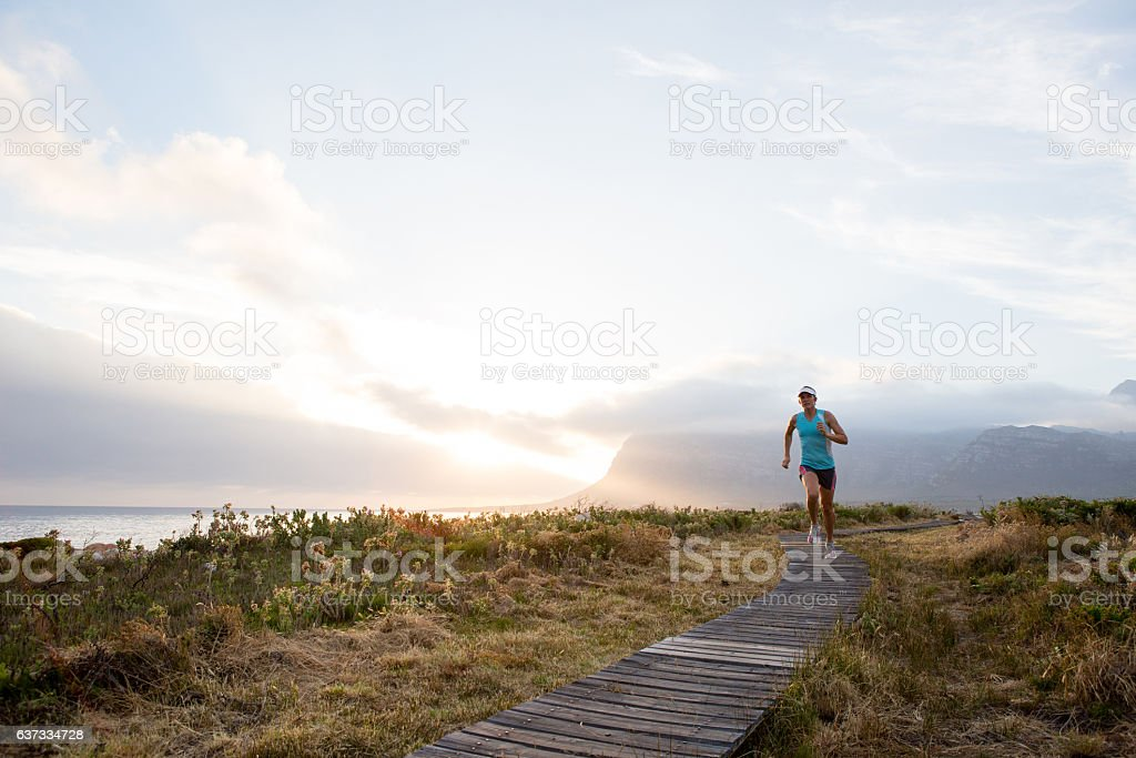 Focused female runs along a beautiful coastal path stock photo