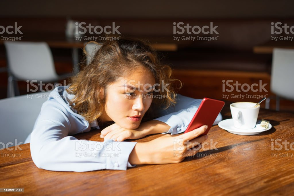 Focused Female Student Using Smartphone at Cafe stock photo