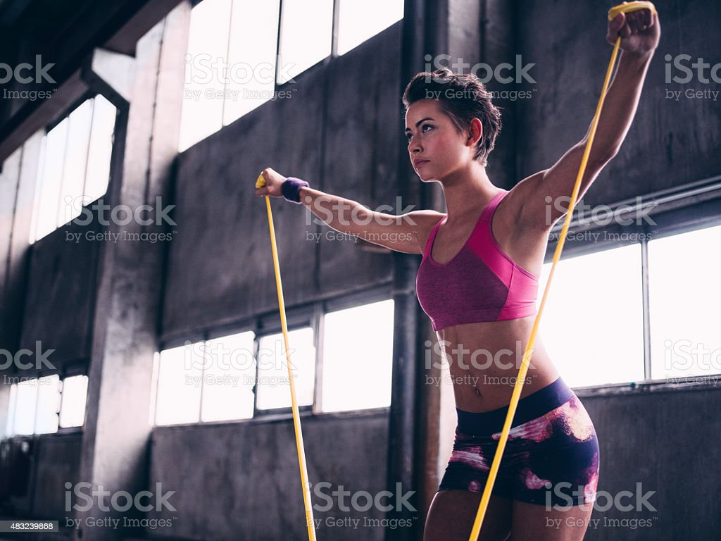 Focused girl in pink sportswear exercising with yellow resistance band stock photo