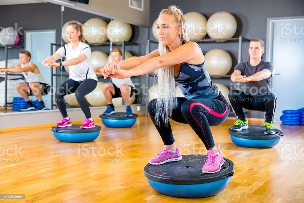 Focused group training squats on half ball at fitness gym stock photo