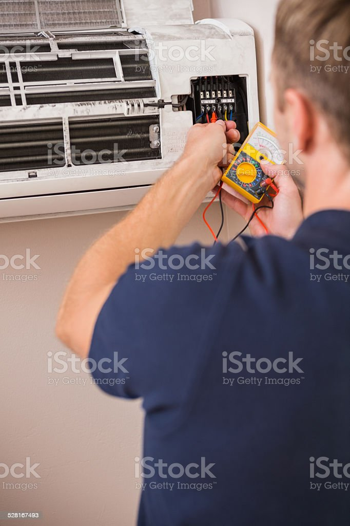 Focused handyman testing air conditioning stock photo