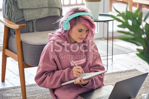 Focused hipster teen girl school college student pink hair wear headphones write notes watching webinar online video conference calling on laptop computer sit on floor working learning online at home.
