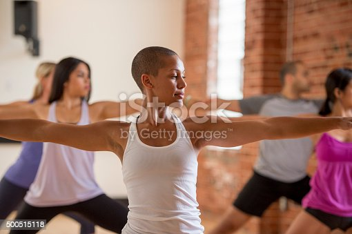 A multi-ethnic group of young adults are standing in warrior two pose during their yoga flow.