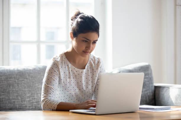 fokuserad indisk kvinna som använder laptop hemma, titta på skärmen - sitta vid dator bildbanksfoton och bilder