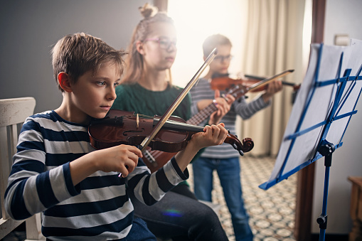 istock Focused kids rehearsing music together 1140433745