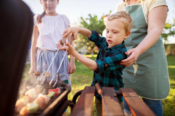 fokussierte kleinen entzückenden kleinkind jungen dreht sorgfältig fleisch und gemüse am spieß auf dem grill, während von seiner fürsorglichen mutter geholfen. - kindergrill stock-fotos und bilder
