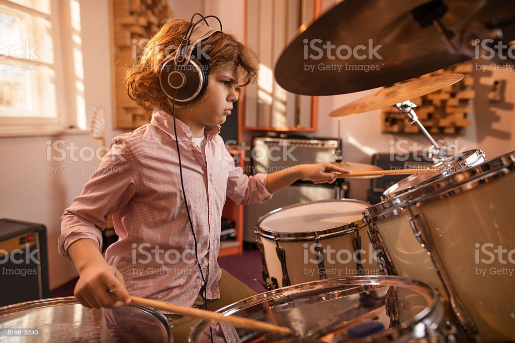 Focused little boy playing drums in music studio. stock photo