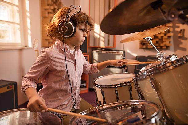 konzentrierte jungen spielen musik schlagzeug im studio. - schlagzeuge stock-fotos und bilder