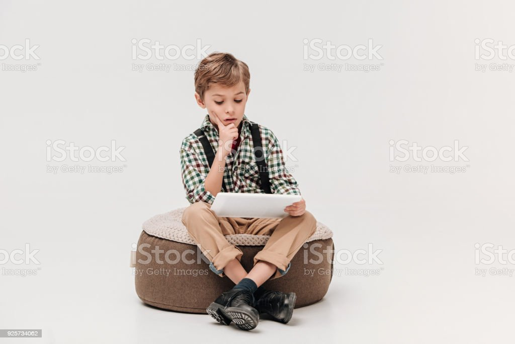 focused little boy sitting and using digital tablet isolated on grey stock photo