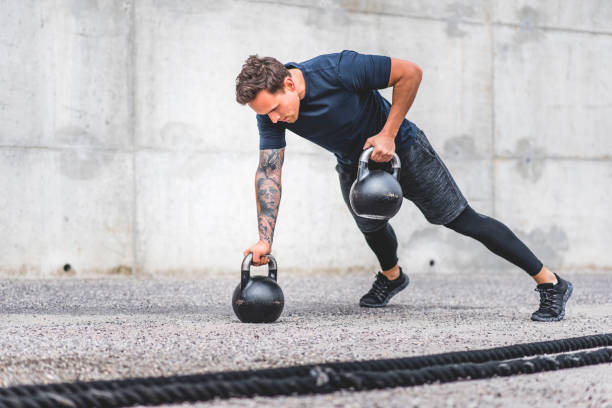 Focused Male Athlete Doing Kettlebell Plank Row Exercise stock photo