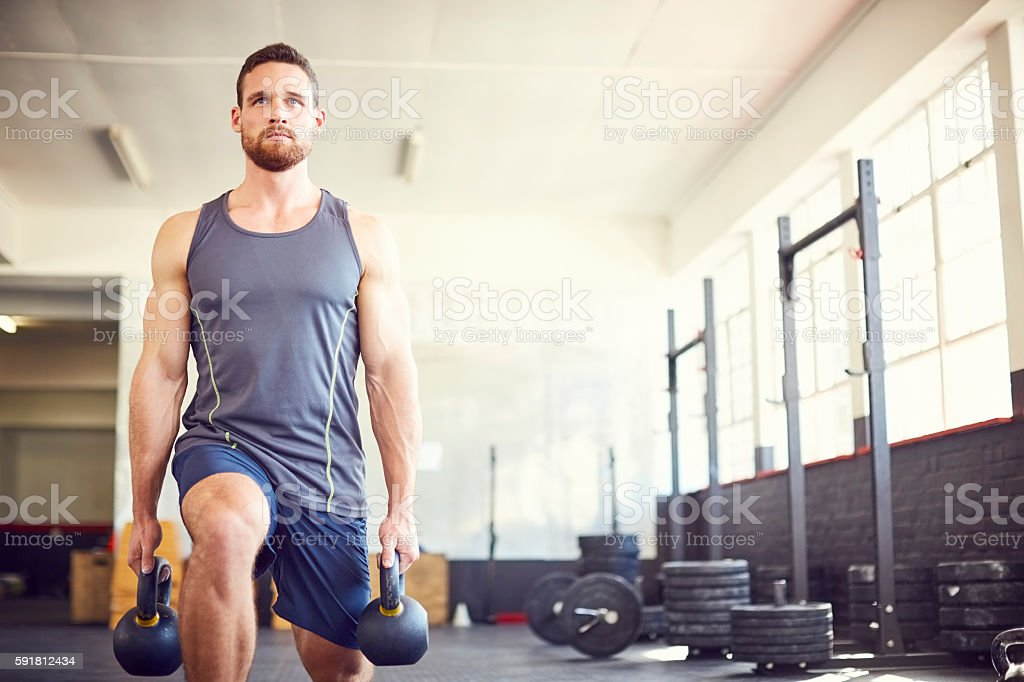 Focused male athlete lifting kettlebells in gym – Foto