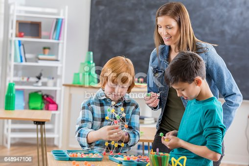 648947070 istock photo Focused male elementary students work on project in class 648947106