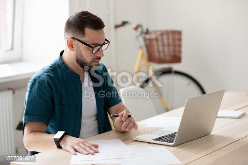 1083827722 istock photo Focused male employee make notes watching webinar 1227091022