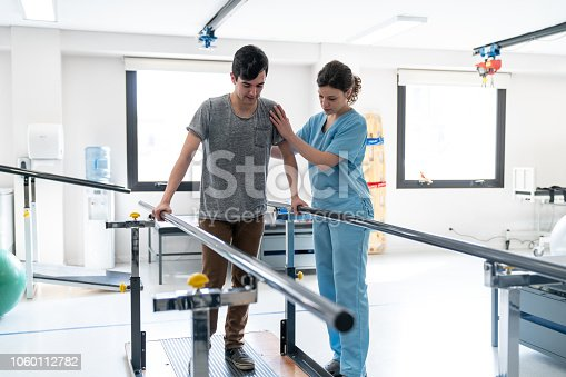 Focused male patient at physical therapy walking with the help of parallel bars and therapist next to him giving support