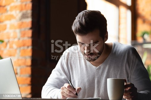 1083827722 istock photo Focused male student make notes studying in cafe 1206334738