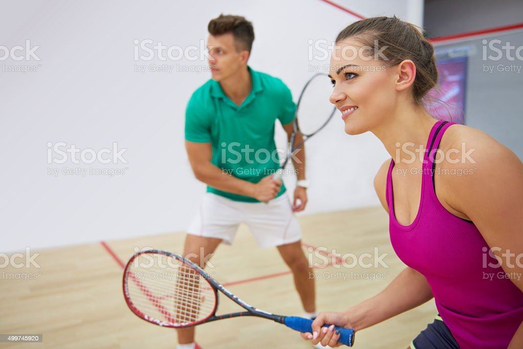 Focused man and woman playing squah together stock photo