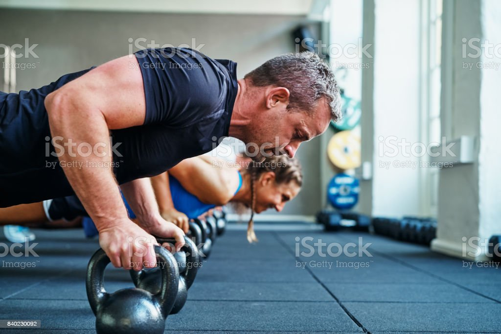 Focused man doing pushups on weights in a gym class stock photo