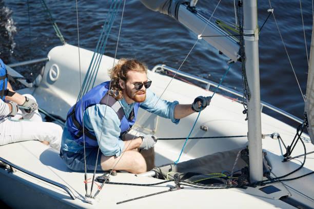 fokussiert man im segelboot - segelhandschuhe stock-fotos und bilder