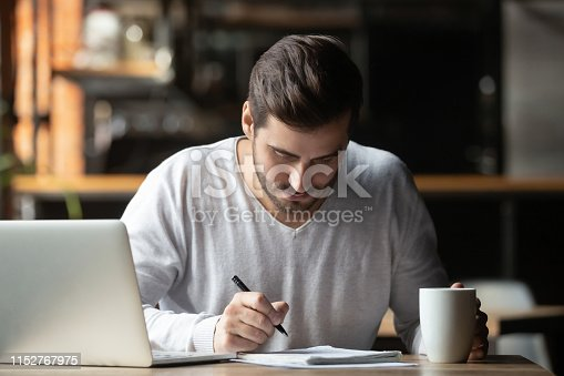 1083827722 istock photo Focused man using laptop and writing notes in coffeehouse 1152767975
