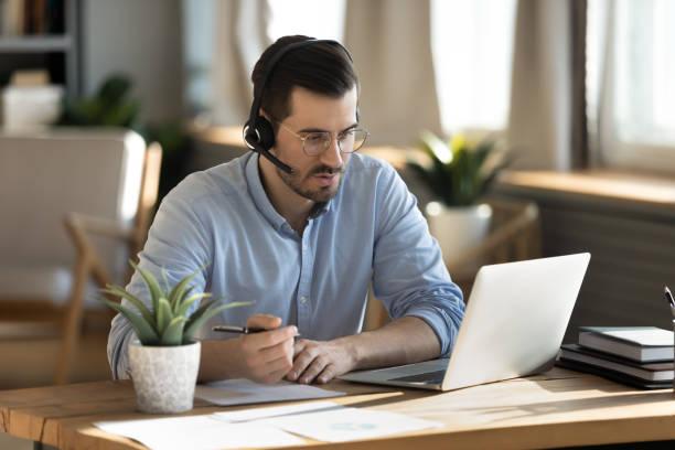 hombre enfocado usando notas de escritura de auriculares, estudiando en línea - sólo hombres jóvenes fotografías e imágenes de stock