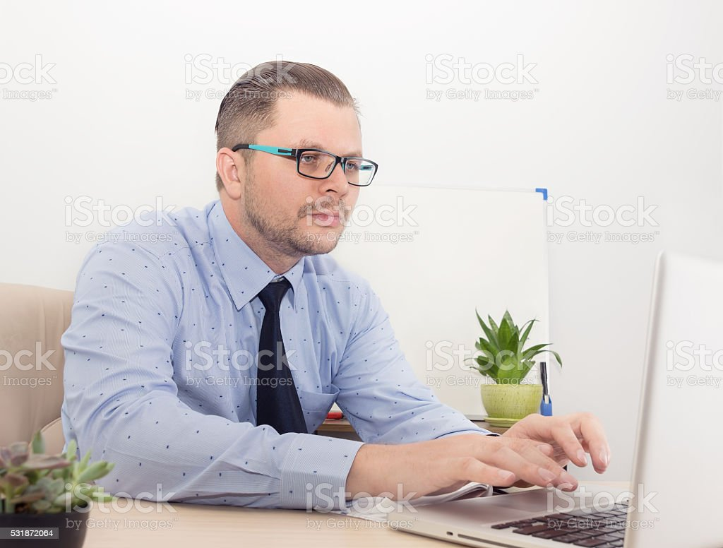 focused manager looking into the laptop screen stock photo