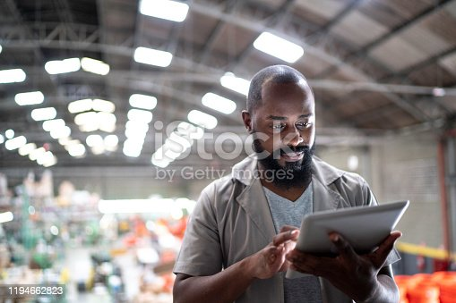 Focused manager using digital tablet in a factory