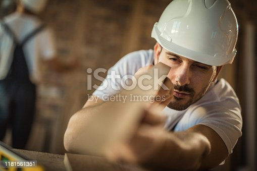 istock Focused manual worker examining wood plank at construction site. 1181561351