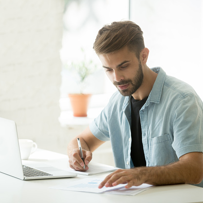 istock Focused marketing manager analyzing statistics working on report making notes 916520182