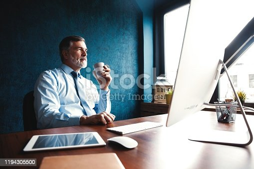Focused mature businessman deep in thought while sitting at a table in modern office
